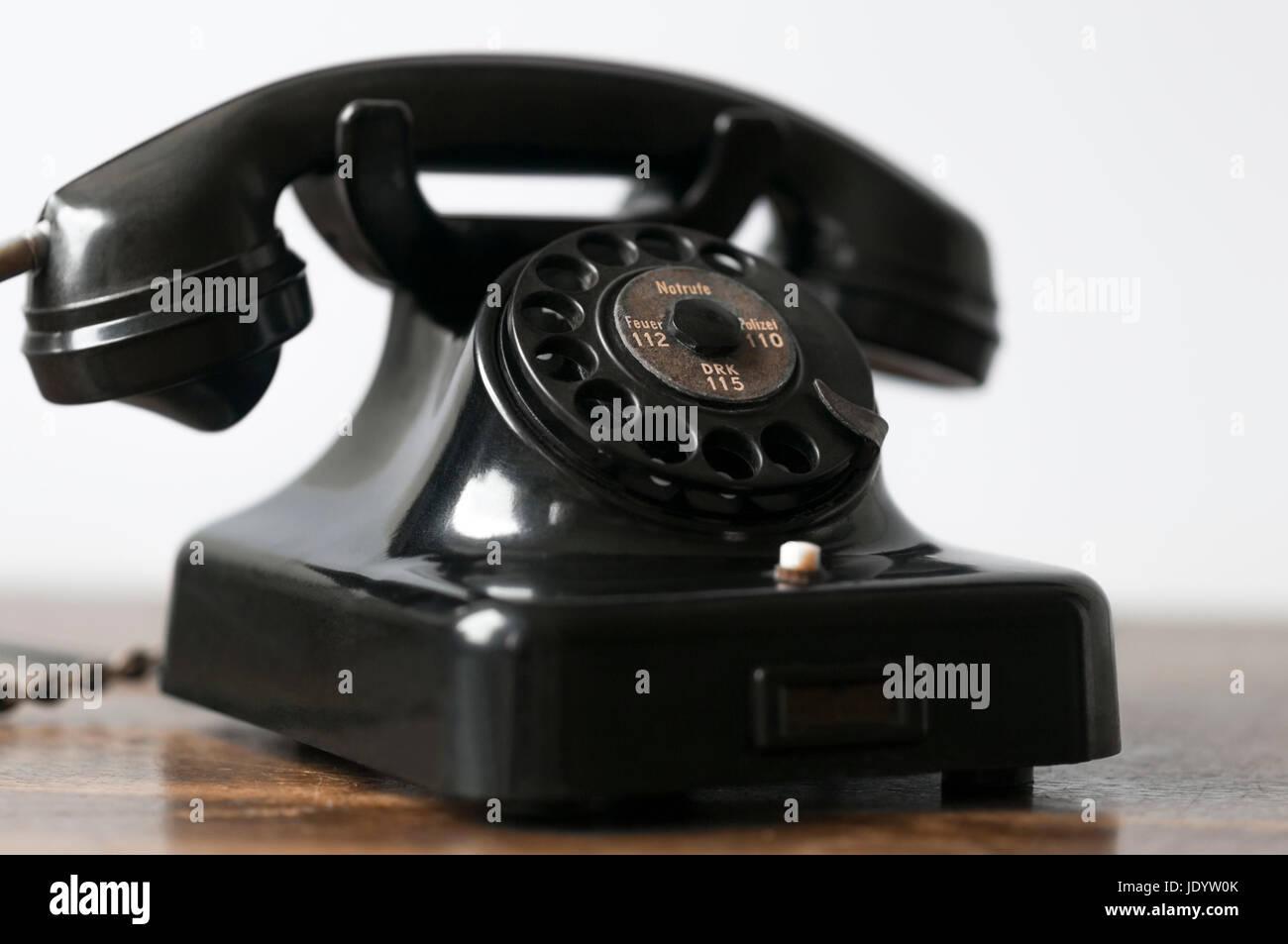 Altes schwarzes Telefon auf einem Schreibtisch und weissem Hintergrund. - Stock Image