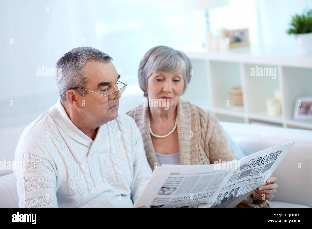 Senior couple reading newspaper together at home - Stock Image