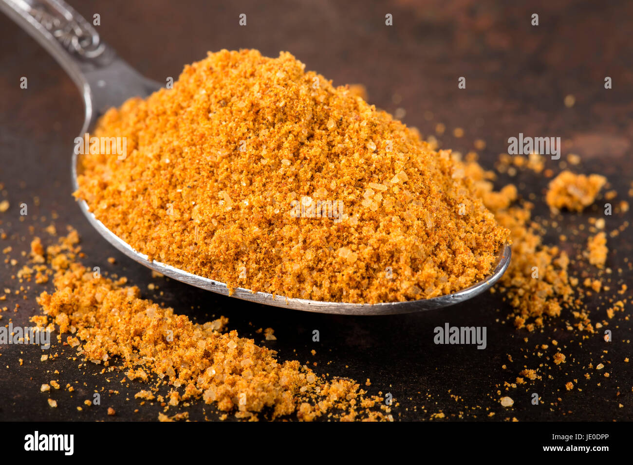 Spoon filled with spices for the preparation of roast on rusty background Stock Photo
