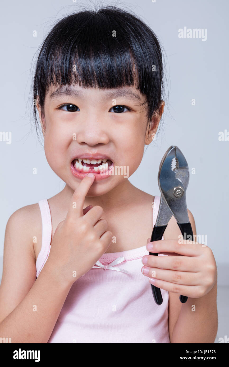 Asian Chinese little girl holding pliers and showing the gap in isolated white background - Stock Image