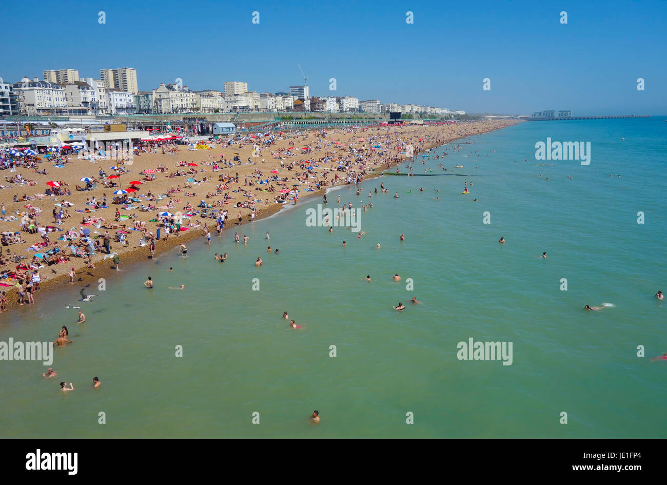 Brighton Beach with people on the beach in recent summer heatwave. - Stock Image