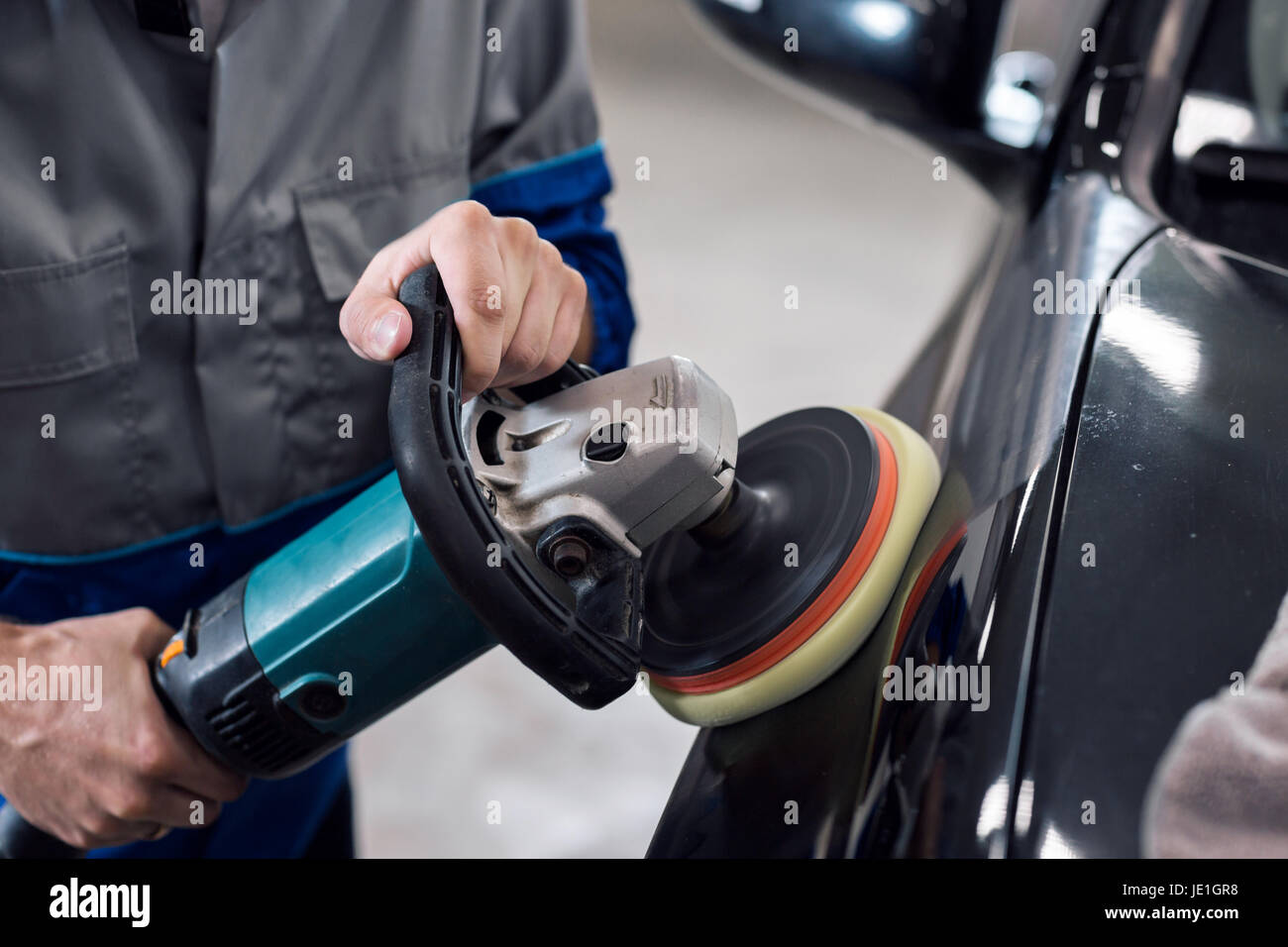 Close-up of hands worker using polisher to polish a black car body in the workshop - Stock Image