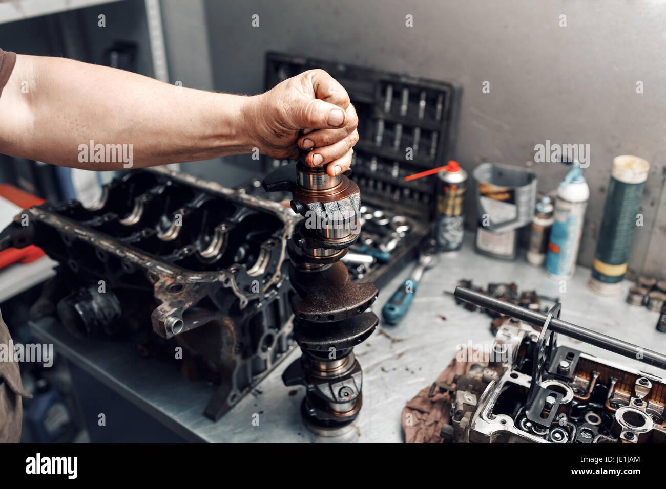 mechanic repairman at automobile car engine maintenance repair work. the crankshaft of the engine - Stock Image