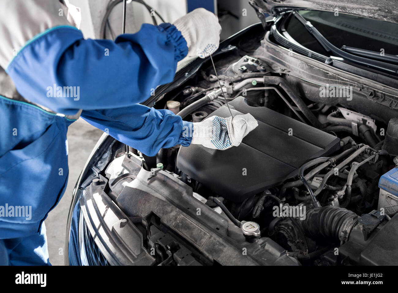 Mechanic checking oil level in a car workshop - Stock Image