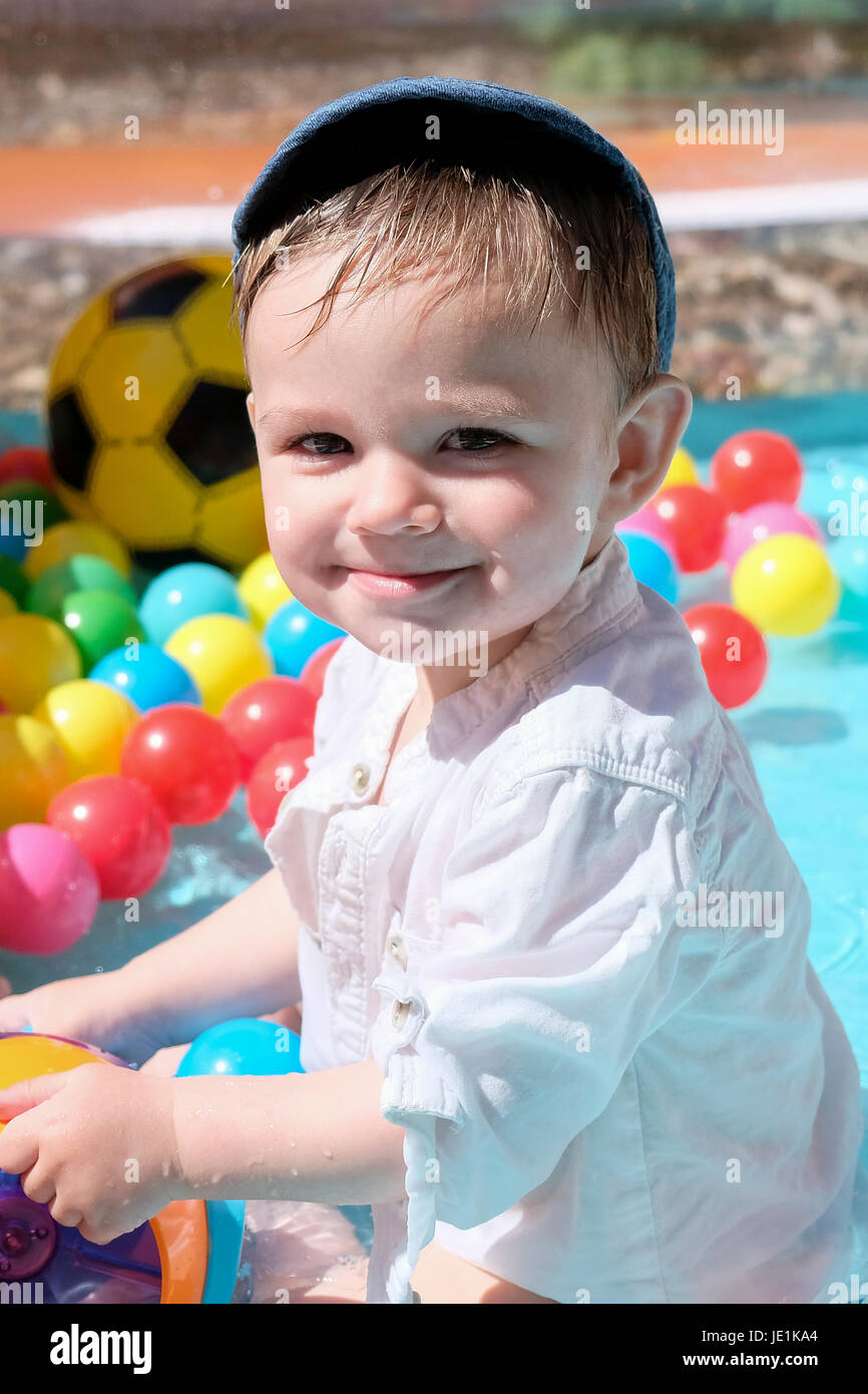 baby boy playing in paddling pool on sunny day - Stock Image