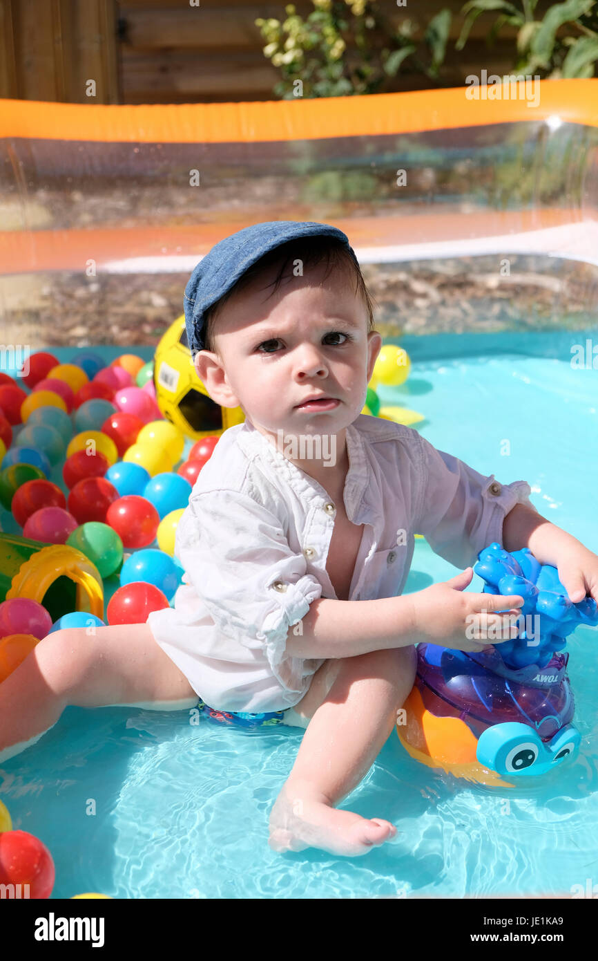baby boy in paddling pool on sunny day - Stock Image