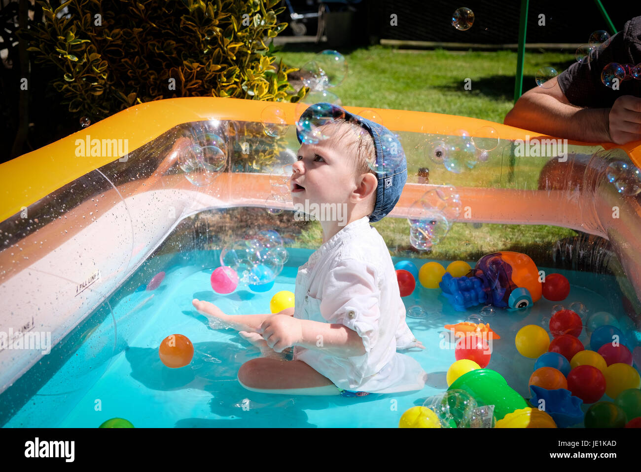 child playing in paddling pool on sunny day - Stock Image