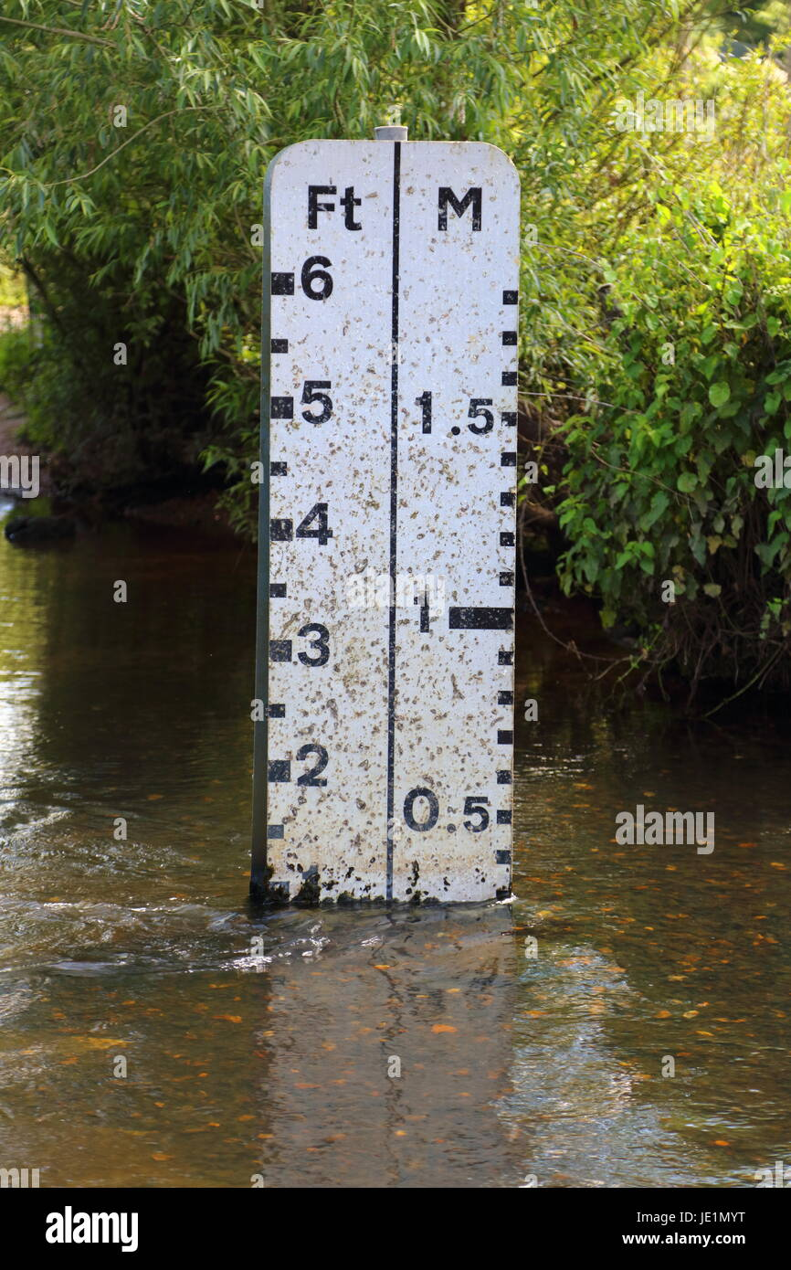 A rural water crossing with roadside depth markers and the depth gauge in reflective material with water depths - Stock Image
