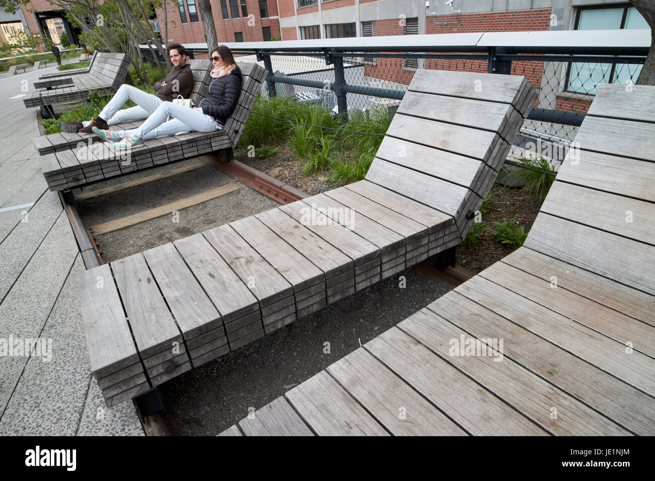 wooden sun loungers on rails on the high line elevated park walkway New York City USA - Stock Image