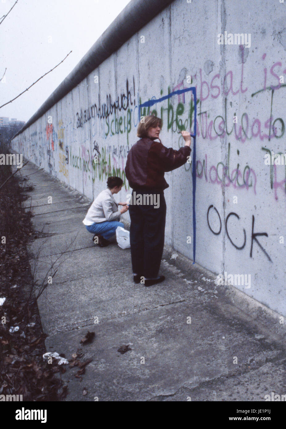 A lady looks at the camera whilst she paints graffiti on the Berlin Wall. October 1987. - Stock Image