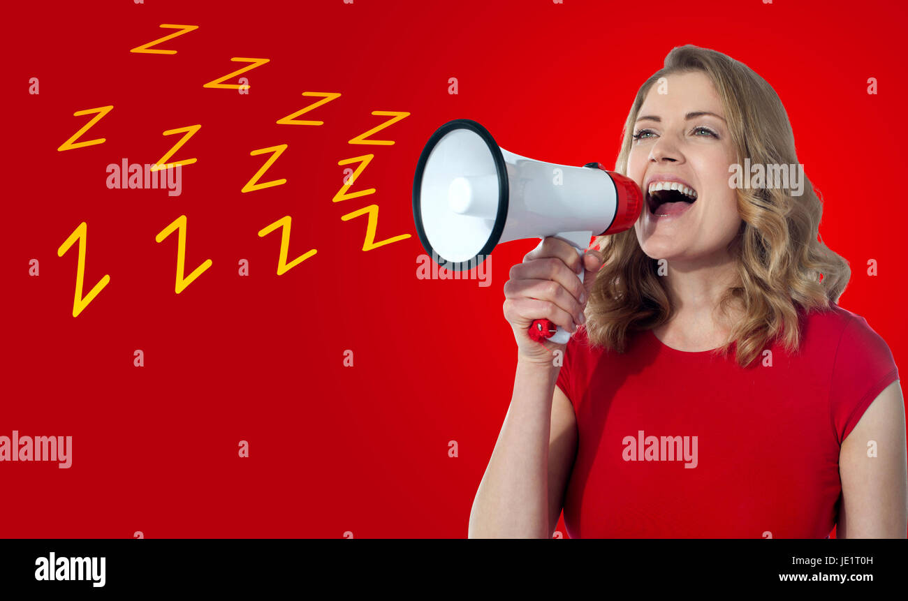 Attractive woman loudly speaking into a megaphone - Stock Image