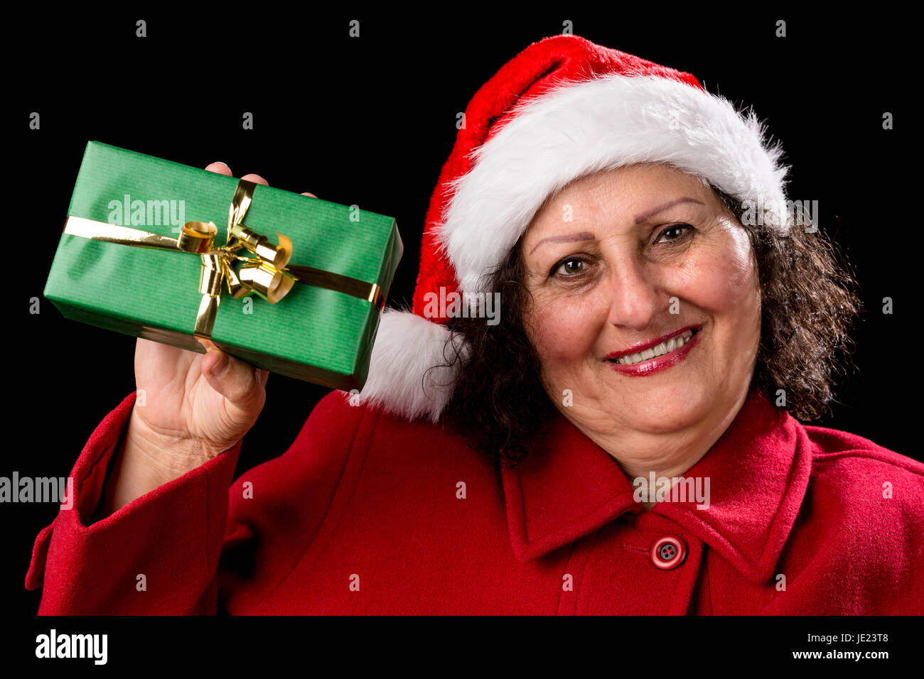 Middle aged woman wearing a Father Christmas hat and a red coat. She is holding up a green Xmas gift with her right - Stock Image