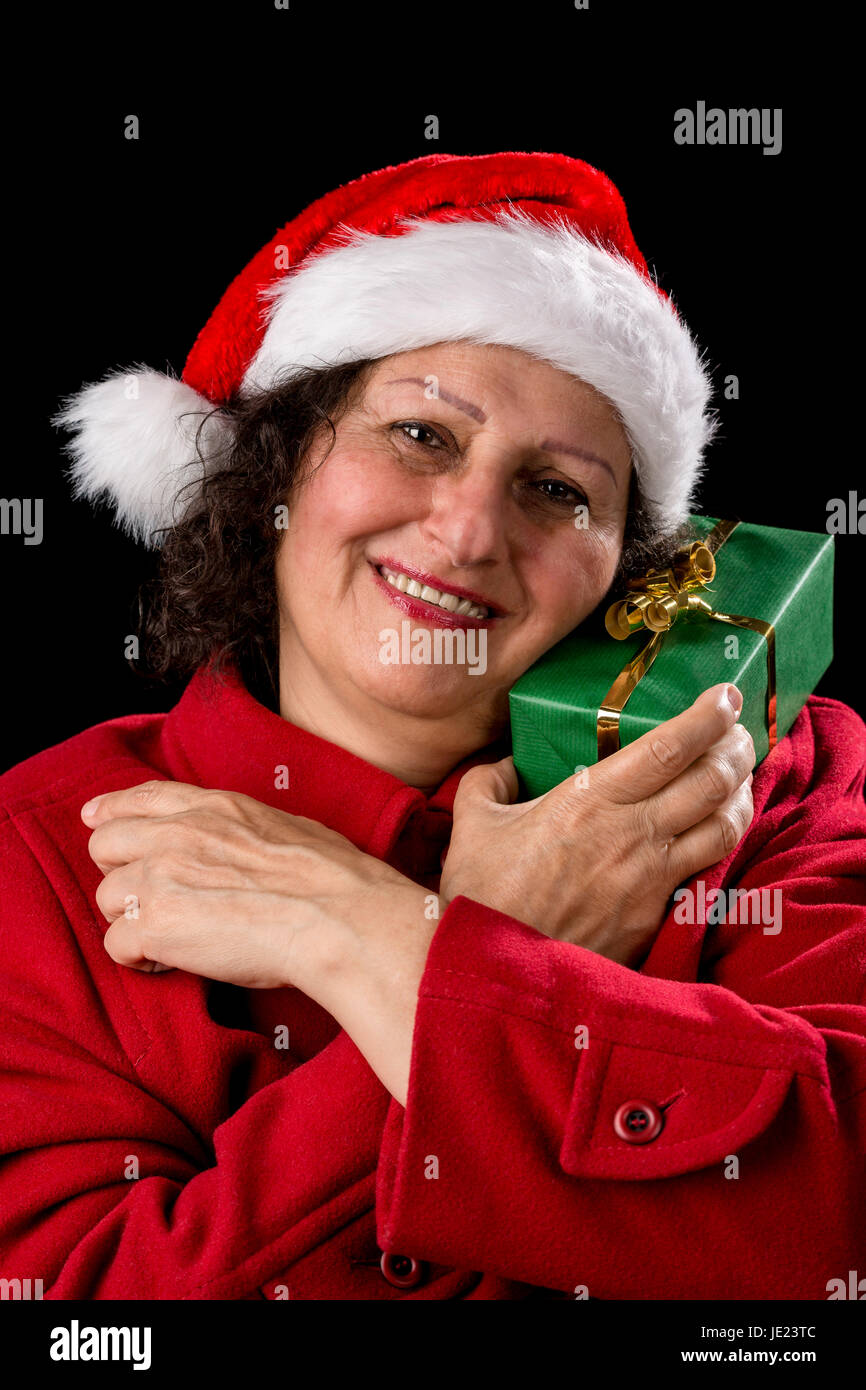 Smiling middle-aged lady is cuddling a green wrapped Christmas present. She is wearing a Santa Claus cap and a red - Stock Image