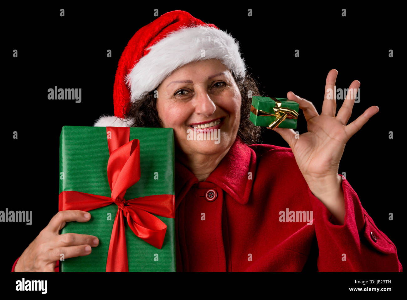 Aged lady is showing two wrapped Xmas presents, one small, one bigger. She is wearing a red coat and a Santa Claus - Stock Image
