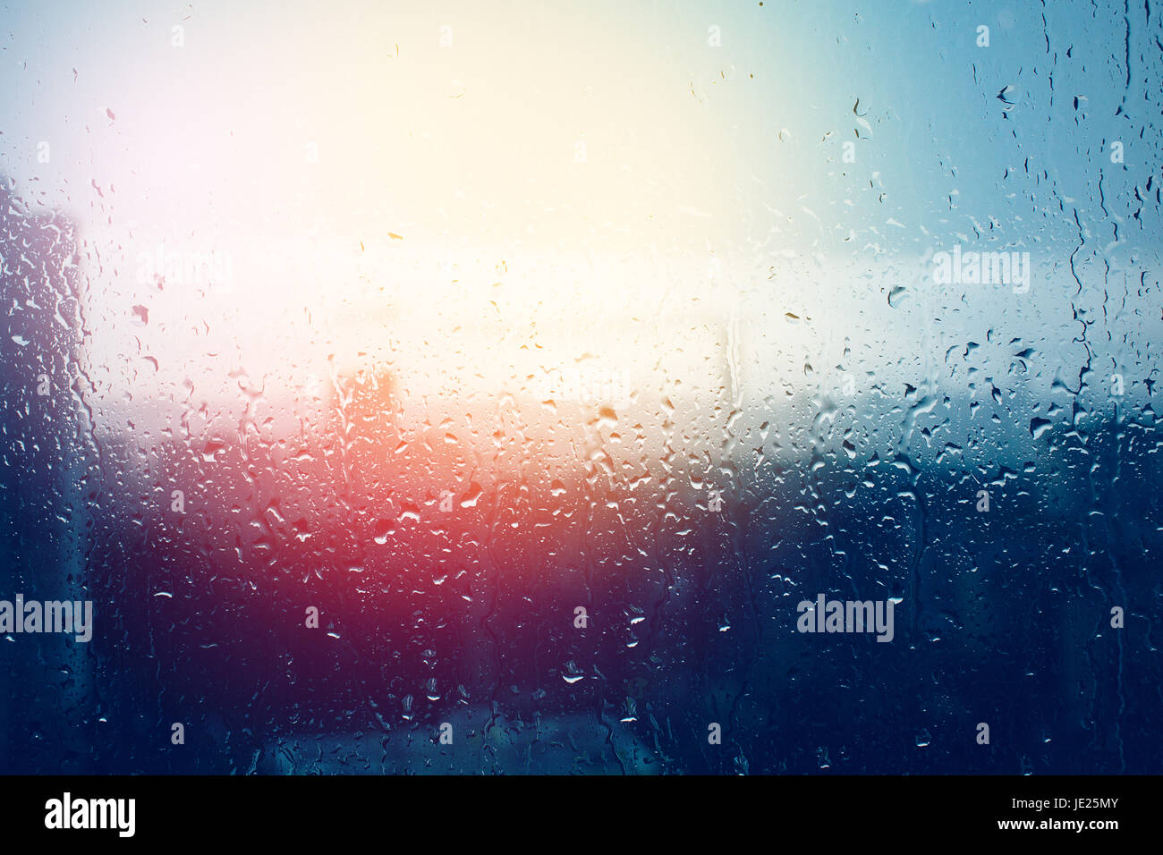 Raindrops on window glass surface, blurred city through window glass after rain - Stock Image