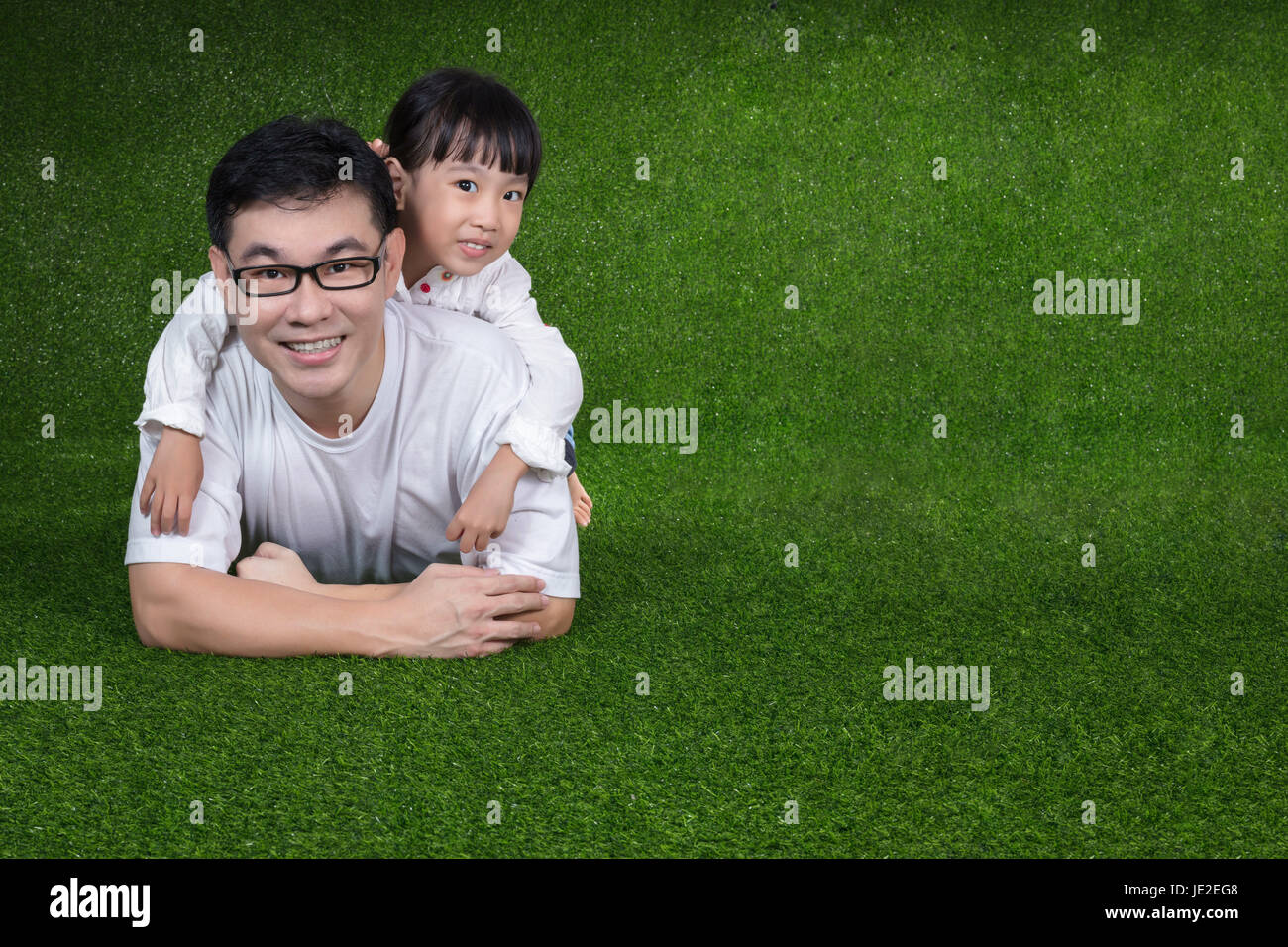 Asian Chinese little girl lying on her father's back at outdoor park - Stock Image