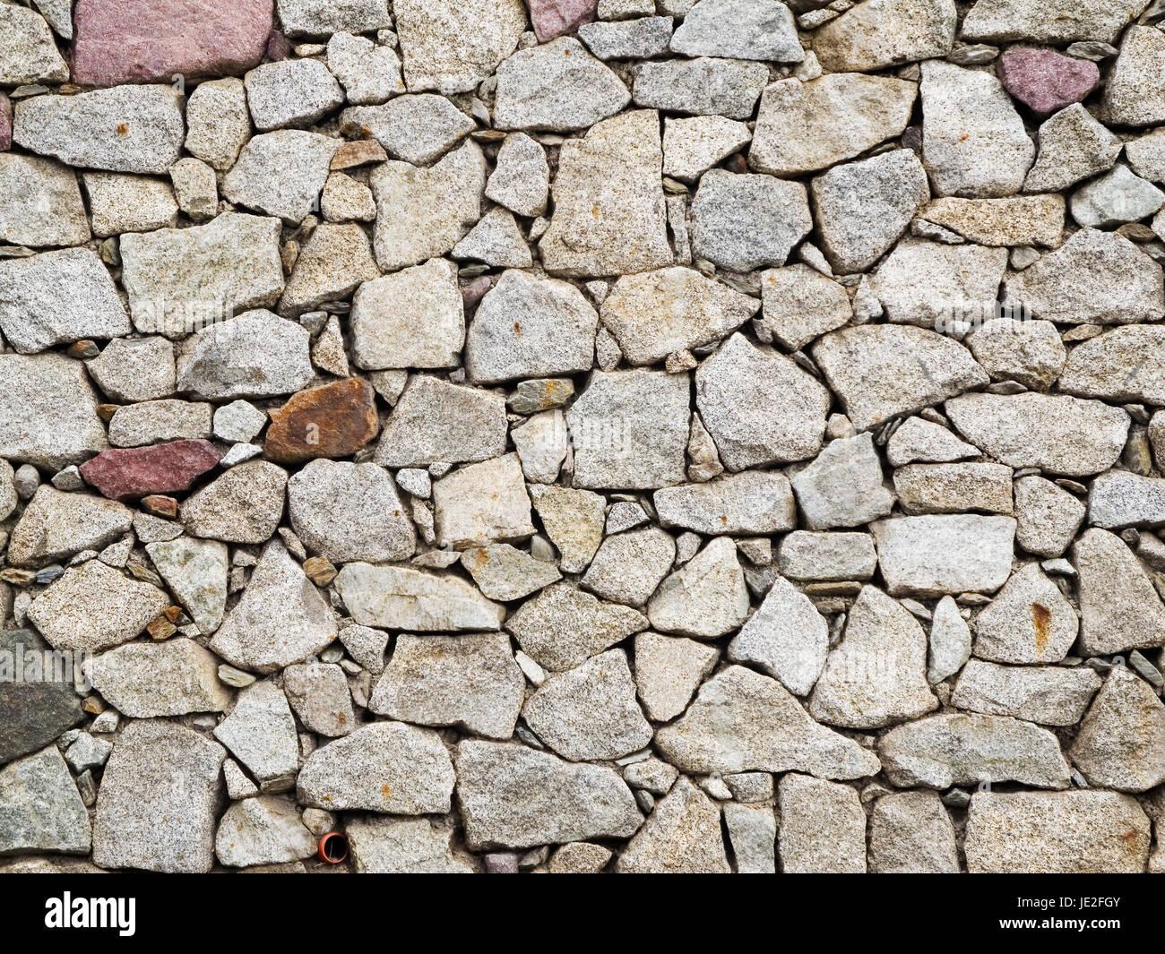 frontale formatfüllende Ansicht einer aus unregelmäßigen Granit-Steinen gemauerten Wand - Stock Image