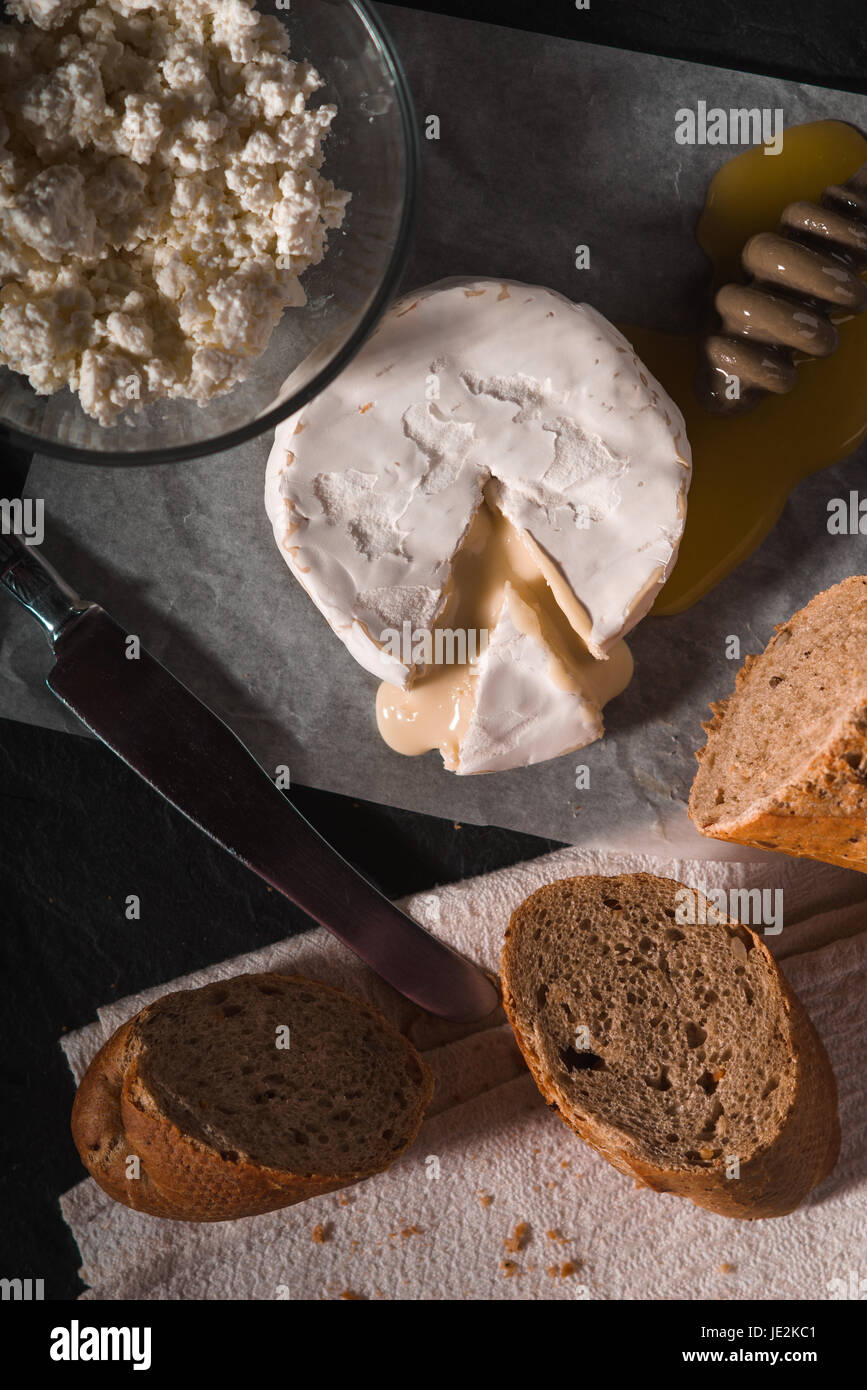 Brie cheese with honey and bread on the background vertical - Stock Image