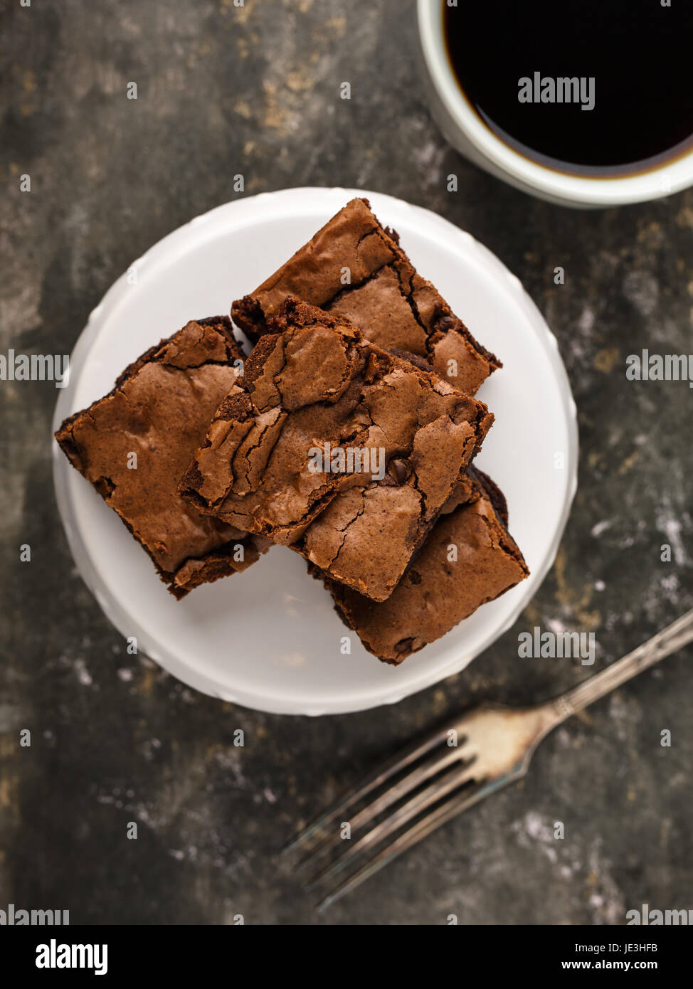 homemade brownies on a dessert plate and coffee. - Stock Image