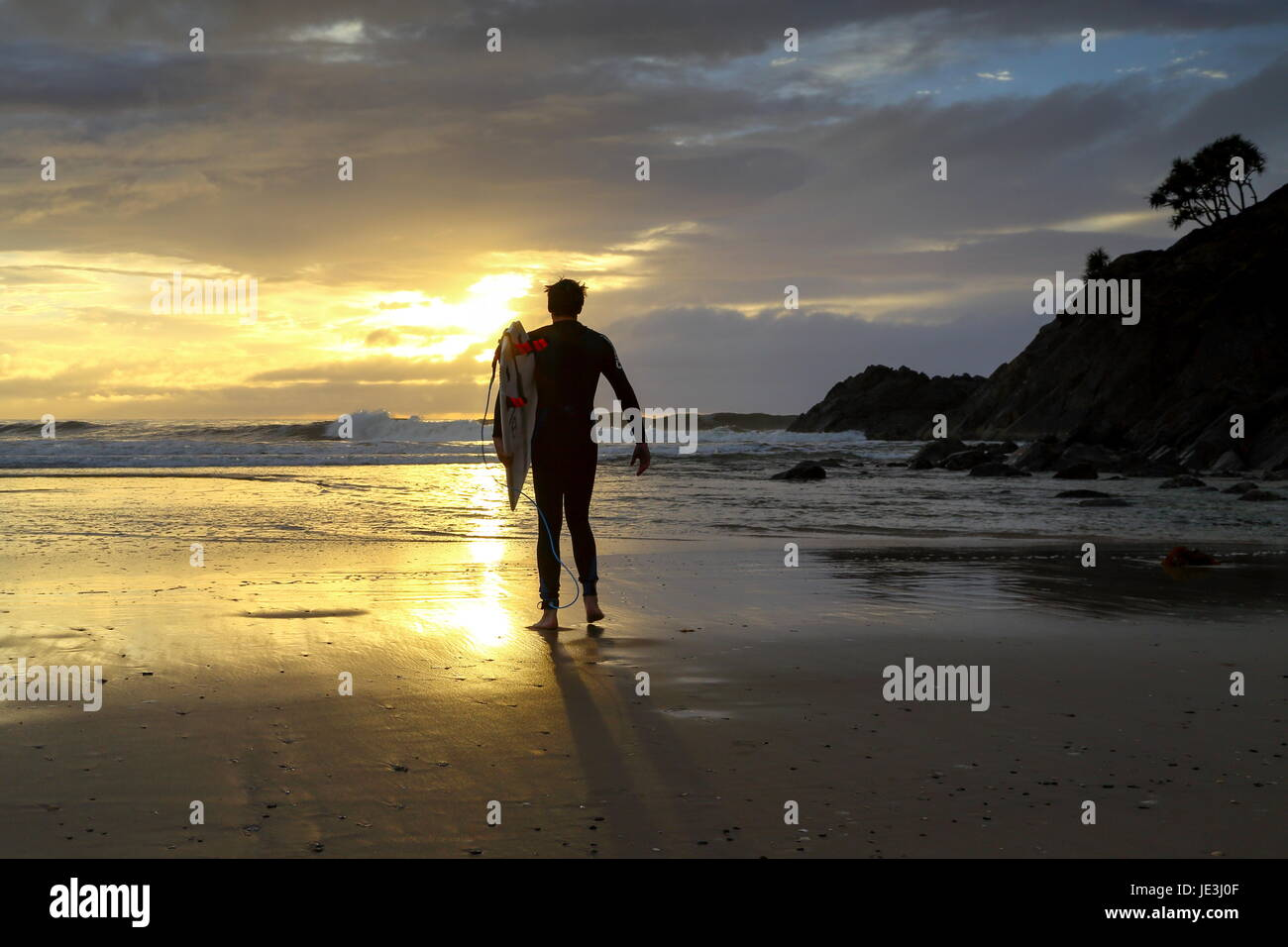 A man in his late twenties walking the beach to go surfing. - Stock Image
