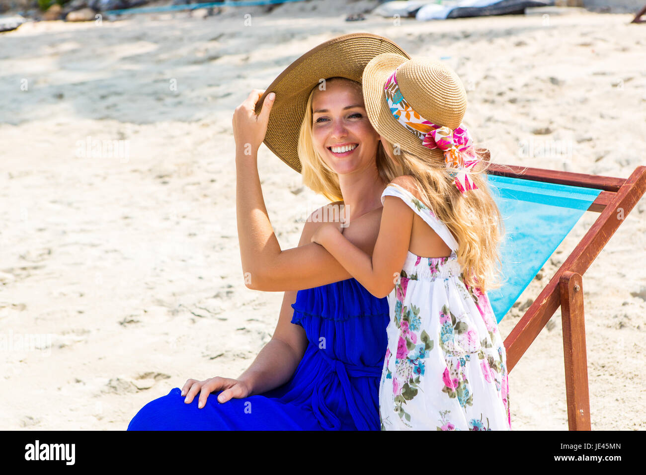 Beautiful mother lady with her pretty blonde cute daughter. Woman sitting in a beach chair and smile. Little girl - Stock Image