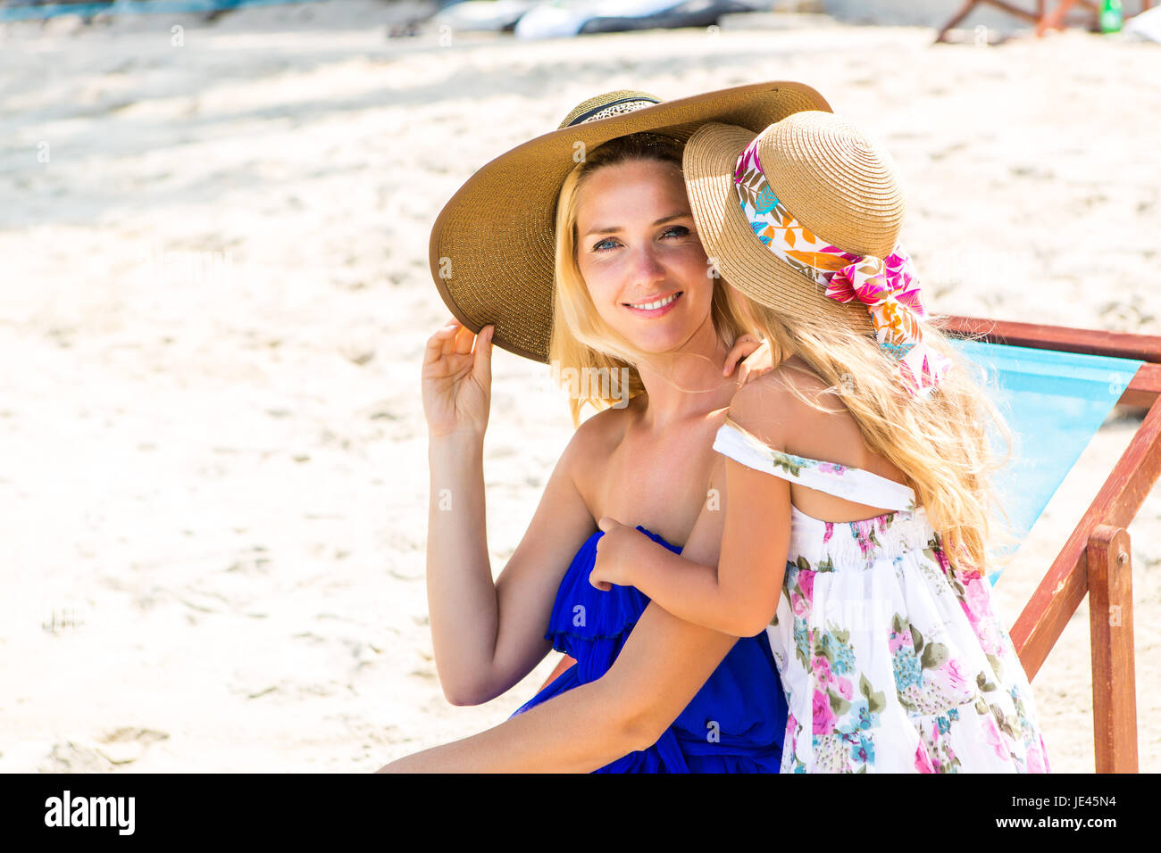 Beautiful mother lady with her pretty blonde cute daughter. Woman in a beach chair smile to the camera. Little girl - Stock Image