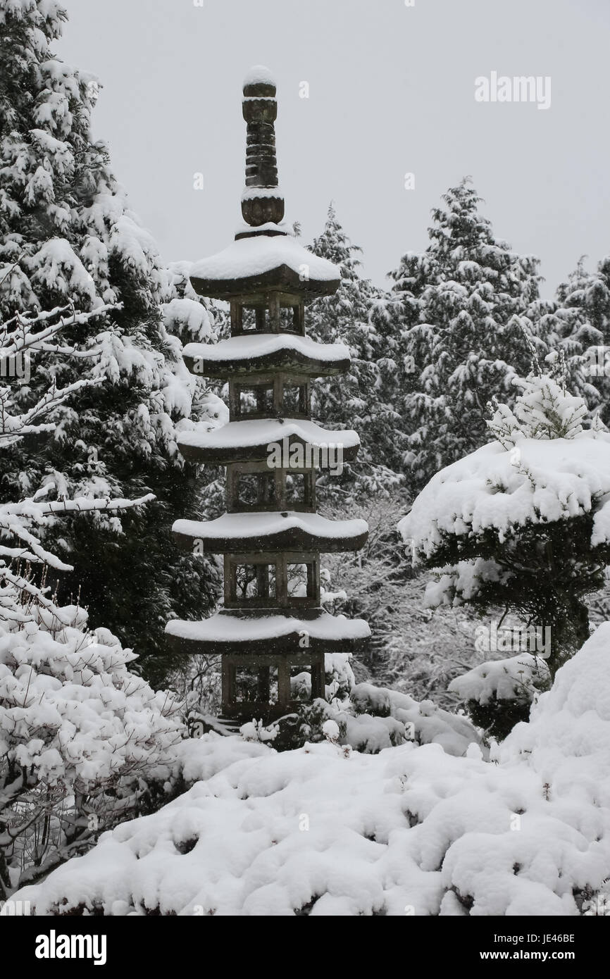 Concrete pagoda garden feature covered with late spring snow in Hakone, Japan surrounded with bushes and trees all - Stock Image
