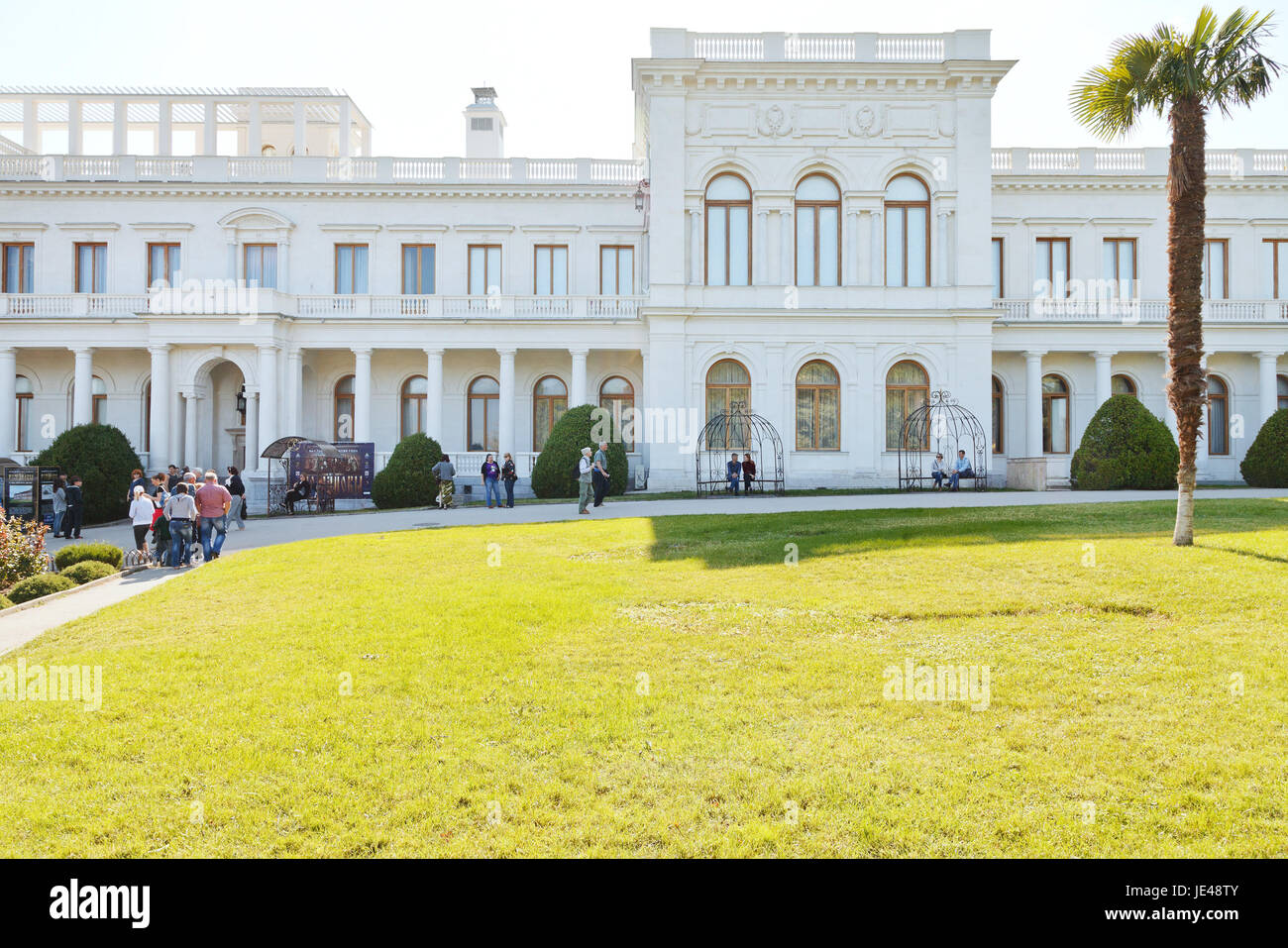 YALTA, RUSSIA - SEPTEMBER 28, 2014: tourists and front view of Grand Livadia Palace in Crimea. Livadia estate was - Stock Image