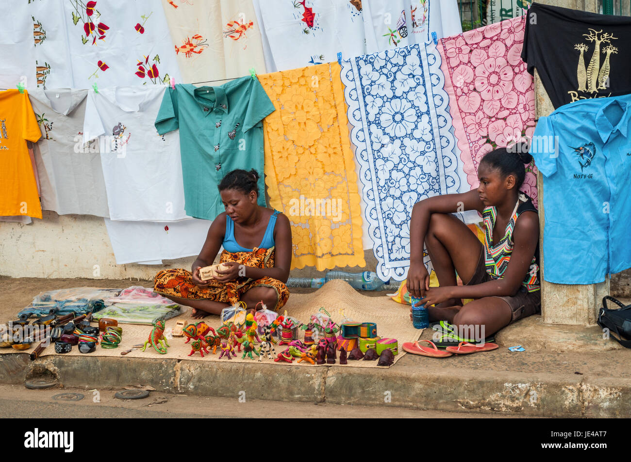 Hell-Ville, Madagascar - December 19, 2015: Indigenous women sell colorful embroidered tablecloths, fabrics and - Stock Image