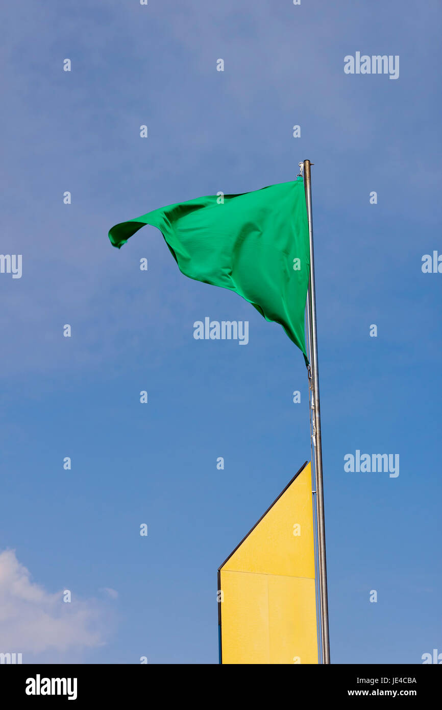 A green flag waving in a yellow mast authorize bathing in the beach. - Stock Image