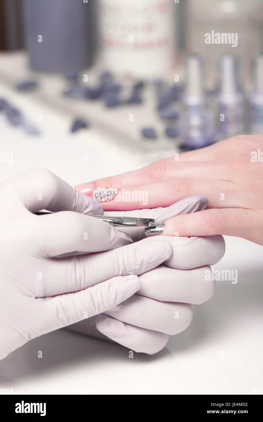 Closeup finger nail care by manicure specialist in beauty salon. - Stock Image