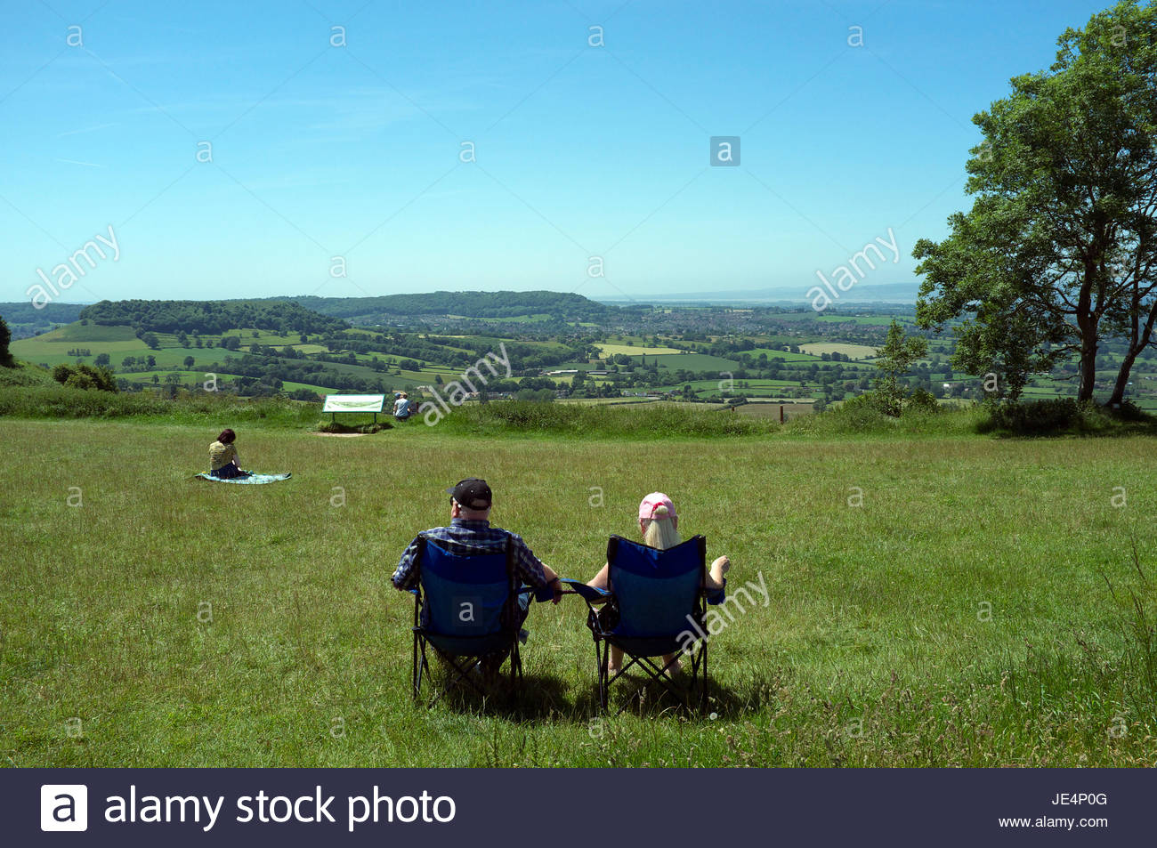 A couple sit in chairs as they look across the Severn Vale, seen from the Coaley Peak pic-nic spot and viewpoint. - Stock Image