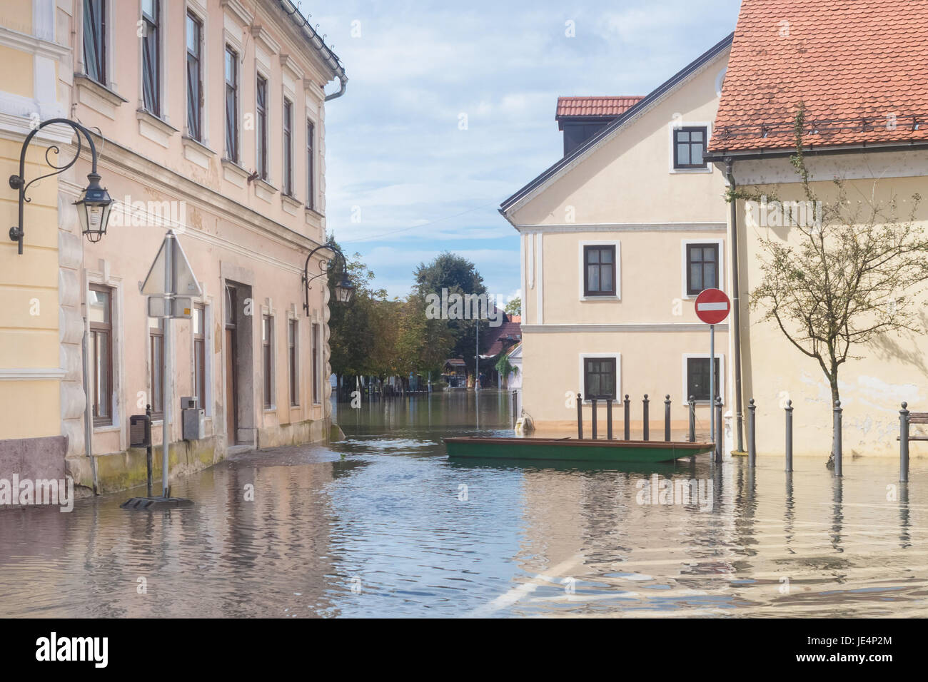 Rural village houses in floodwater. Road with the river overflown with the residents in their homes. Floods and - Stock Image