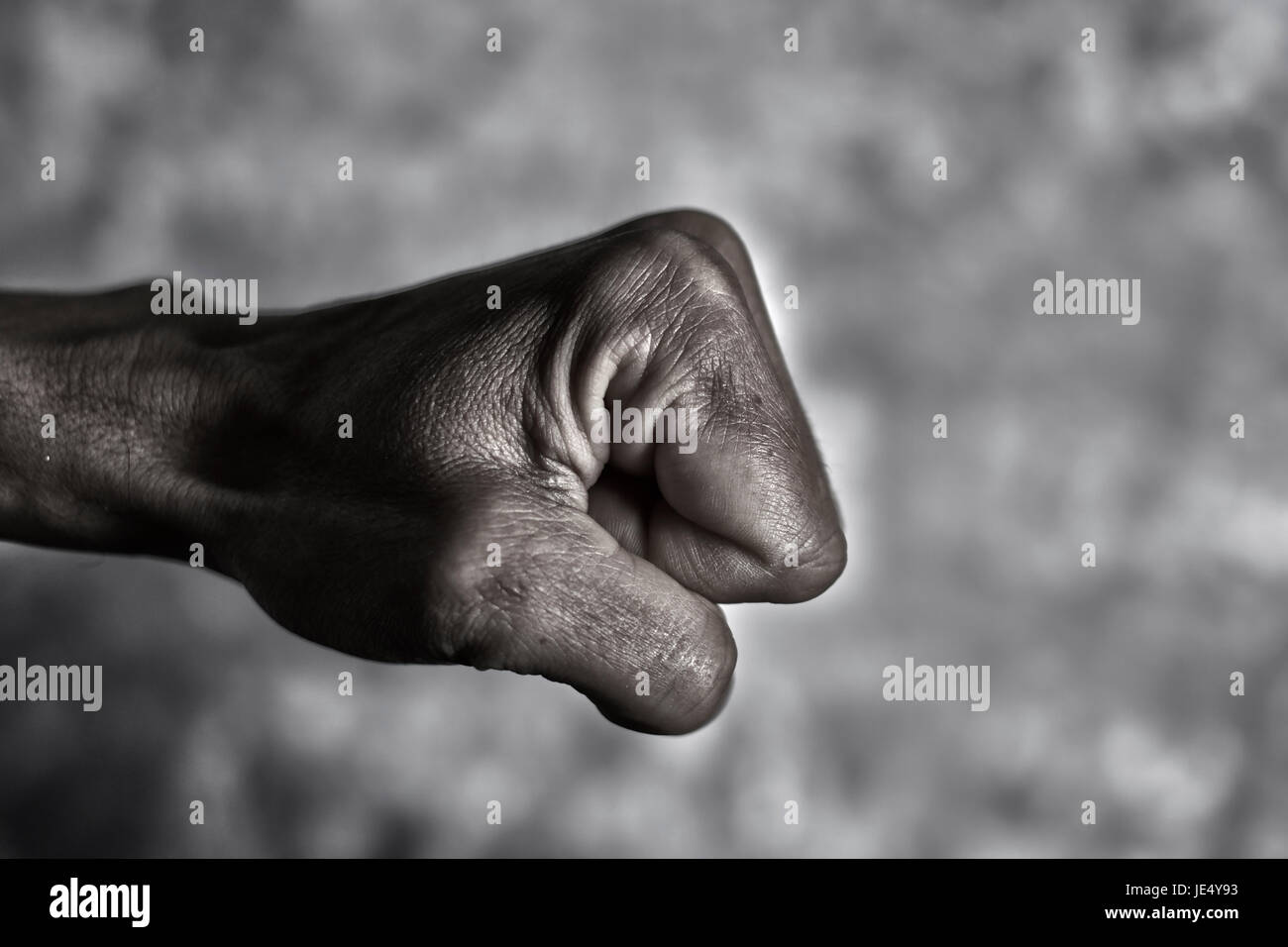 closeup of the fist of a young caucasian man in the air ready to punch or fight, against a graded gray background, - Stock Image
