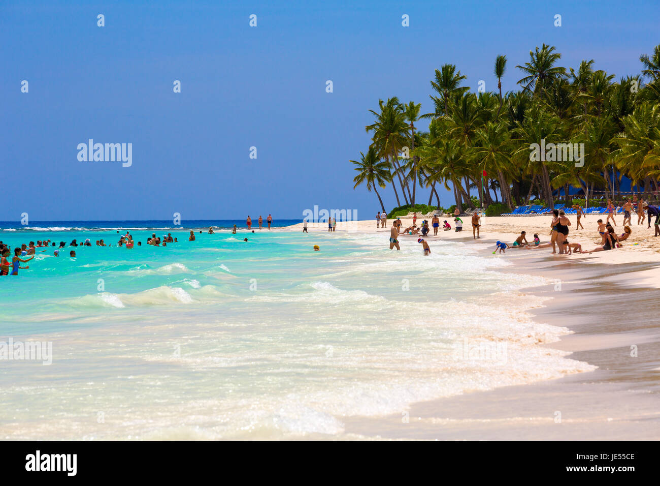 beach of the island Saona with tourists on the hot summer day. - Stock Image