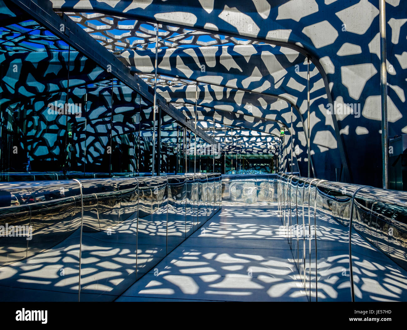 Corridor made of steel, glass,concrete lattice wall with shadow pattern creating by the sun entering the building, - Stock Image