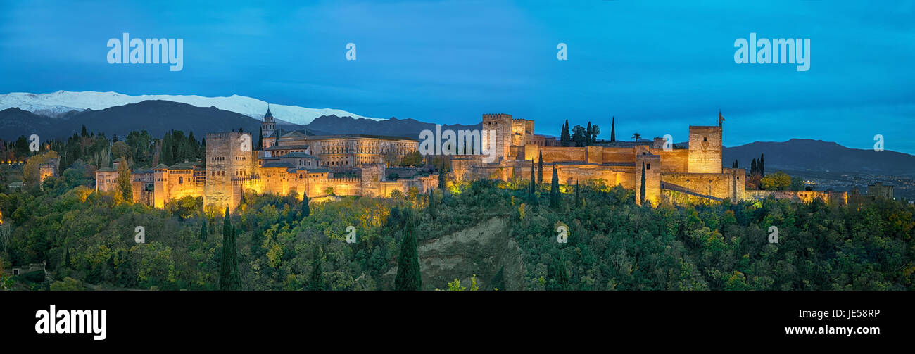 Panorama of Alhambra - medieval Moorish fortress surrounded by yellow autumn trees illuminated in the evening, Granada, Stock Photo