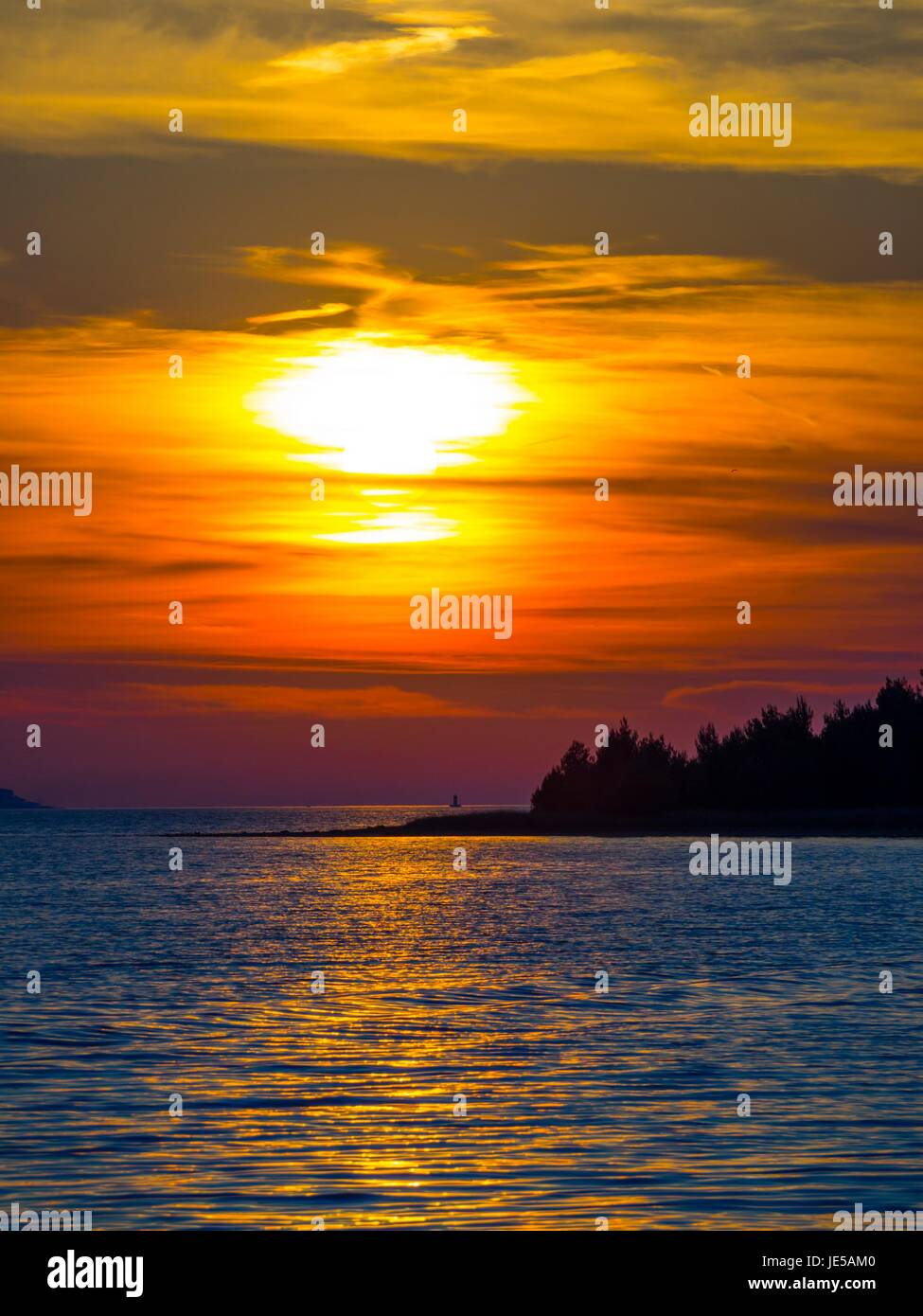 Sunset behind island Stock Photo