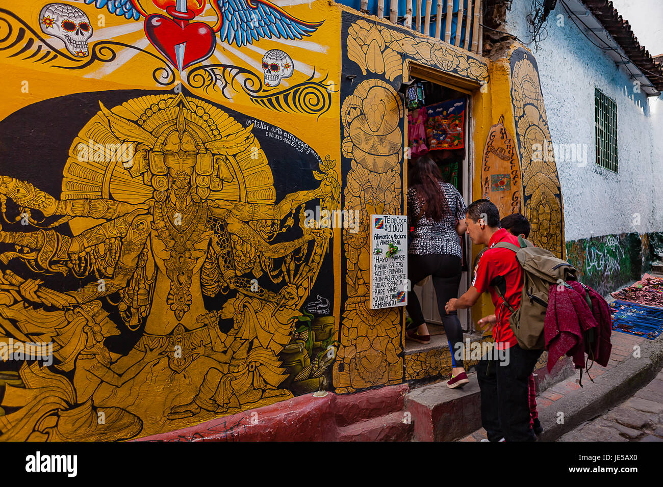 Bogotá, Colombia - A tourist checks a list outside a traditional shop in the narrow, colourful, cobblestoned - Stock Image