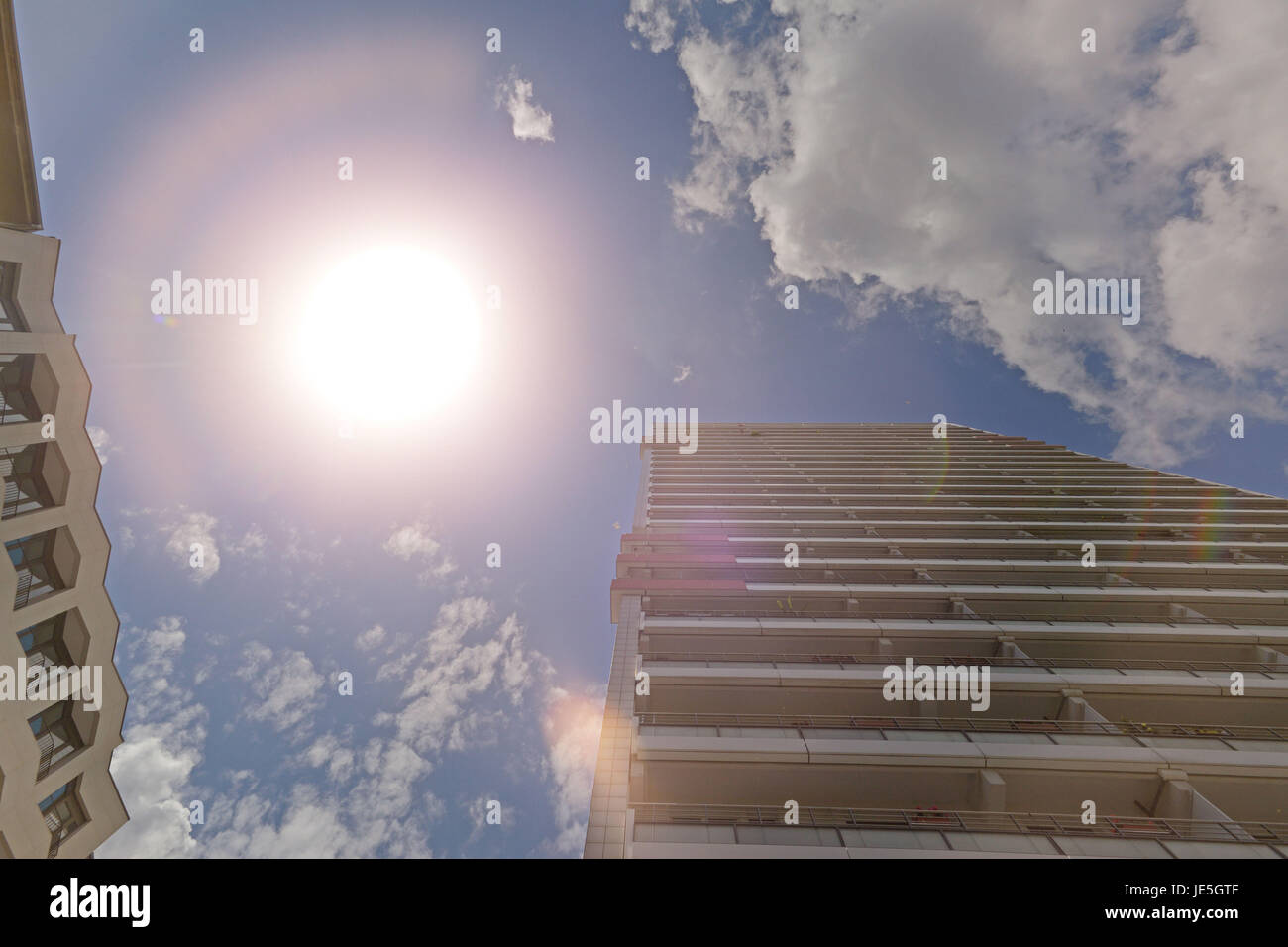 The facade of a high building with some windows closed - Stock Image