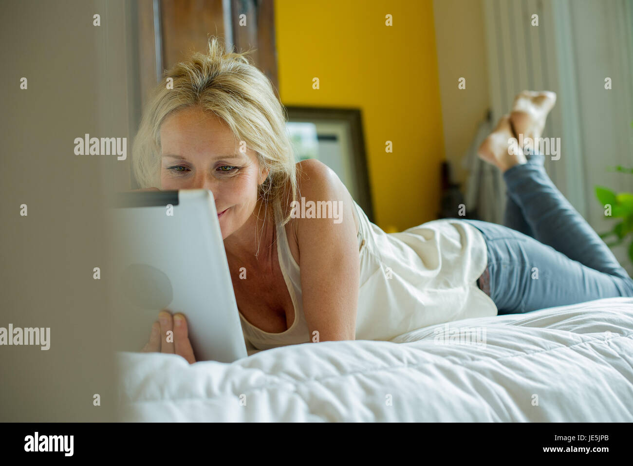 Mature woman lying on bed watching digital tablet - Stock Image