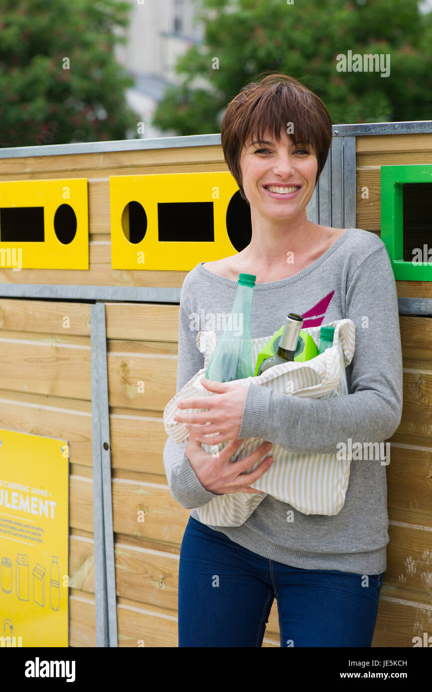 Woman taking recyclables to recycling bin - Stock Image