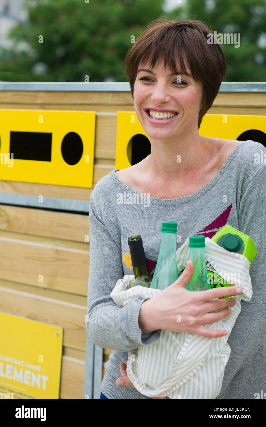 Woman bringing recyclables to recycling center - Stock Image