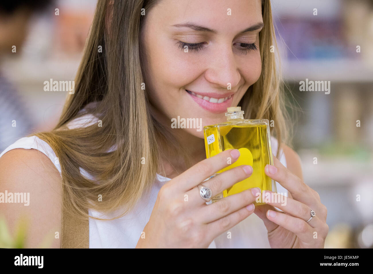 Young woman smelling perfume in shop Stock Photo