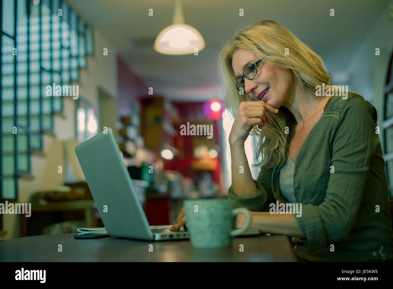 Woman using laptop computer at home - Stock Image