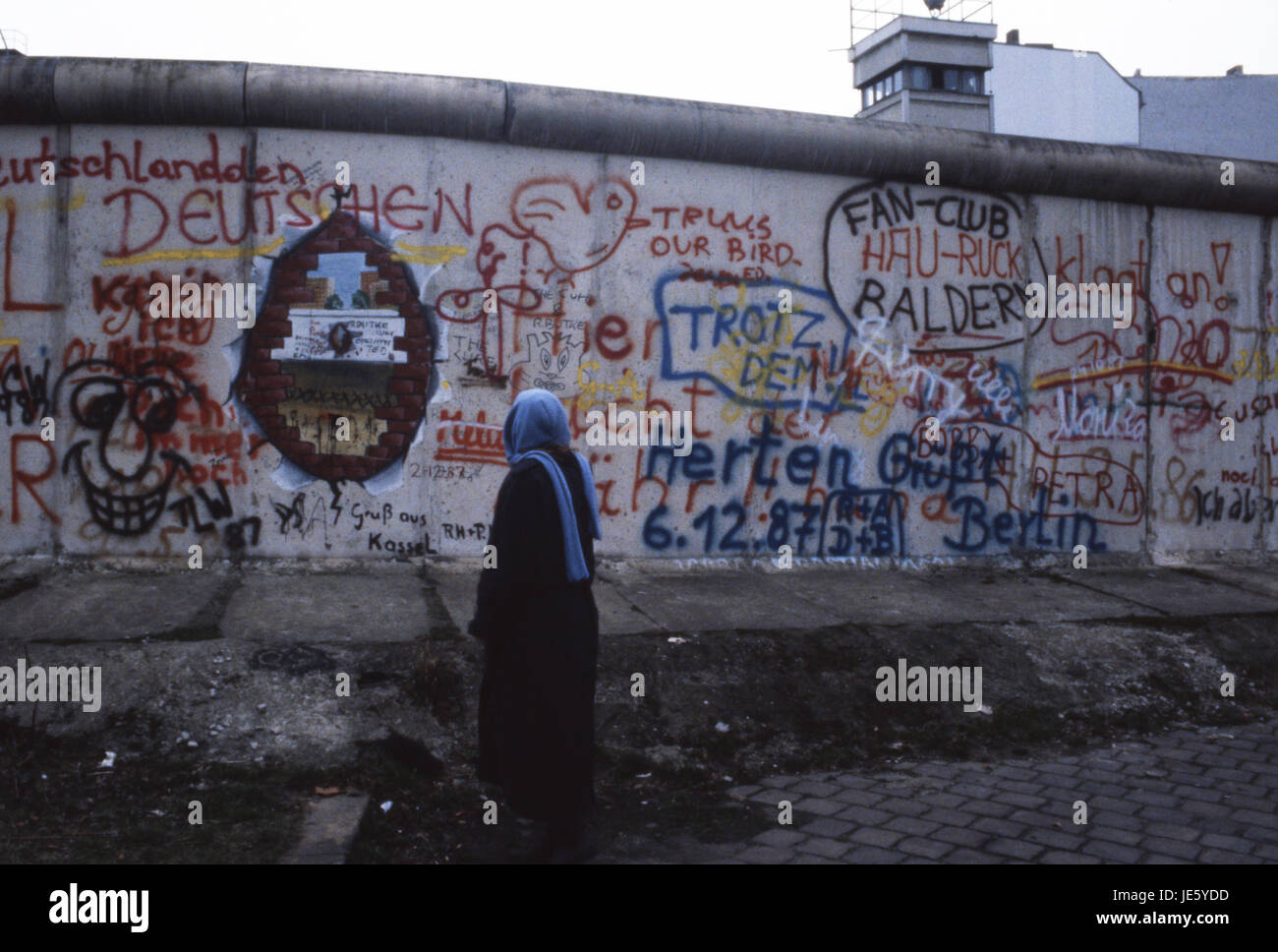 A lady reads the graffiti on the Berlin Wall, whilst East German boarder guards look on. Berlin 1987 Stock Photo