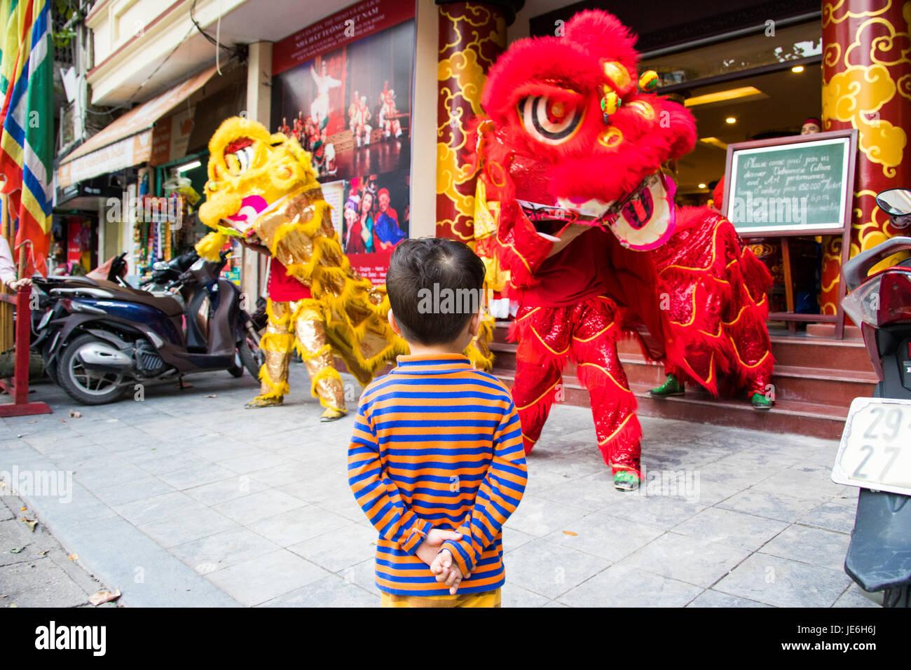 Young boy enjoying a dragon dance in Hanoi, Vietnam - Stock Image