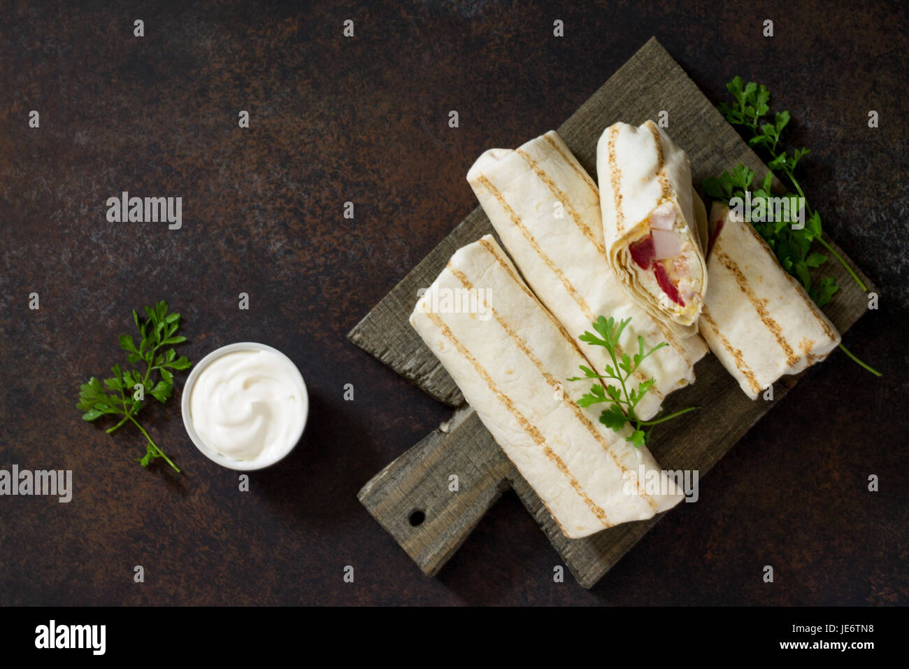 Shawarma pita bread with grilled chicken, fresh vegetables and cream sauce on a background of brown stone. Top view - Stock Image