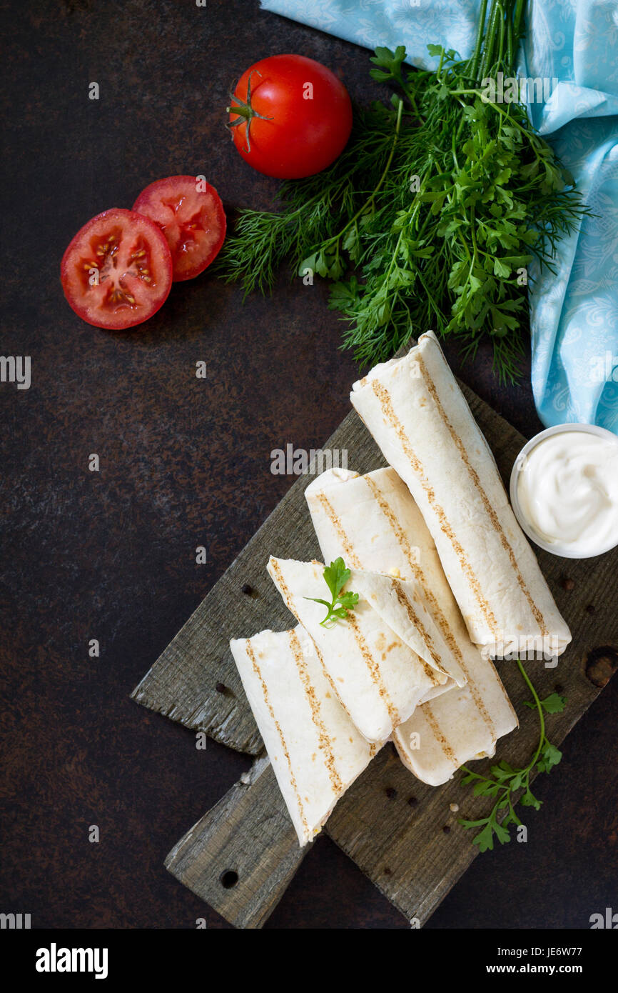 Shaurma lavash with fried chicken meat, fresh vegetables and creamy sauce on a background of brown stone. Copy space. - Stock Image
