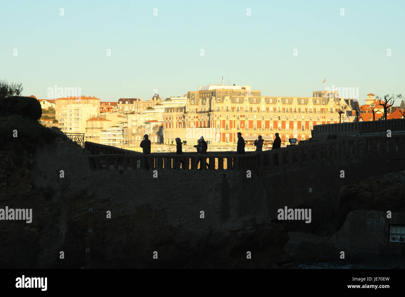 Hotel Du Palais, and silhouettes of people crossing the Rocher du Basta path, Biarritz, France - Stock Image